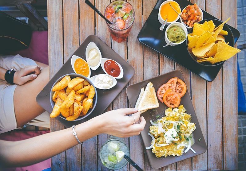 Girl picking up toast from a table spread with vegetarian Mexican food