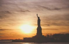 Statue of Liberty silhouetted against a sunrise
