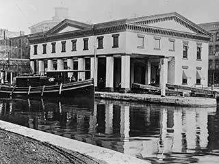Historic image of the Erie Canal Weighlock Building before the canal was paved over