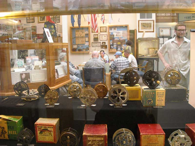 Glass display case filled with fly fishing reels at Catskill Fly Fishing Center & Museum