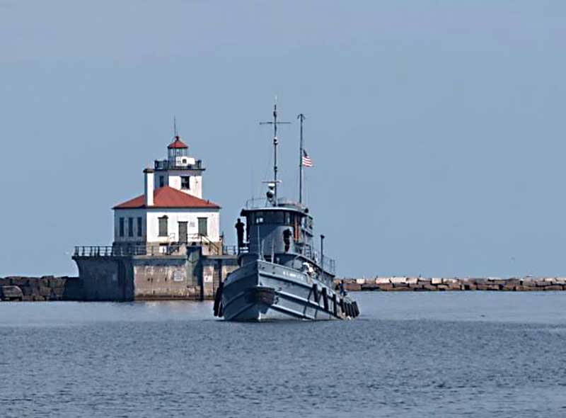 The Major Elisha K. Henson sails on Lake Ontario near Owsego Harbor West Pierhead Light