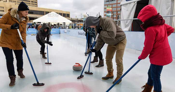 A family learning the sport of curling on an ice rink