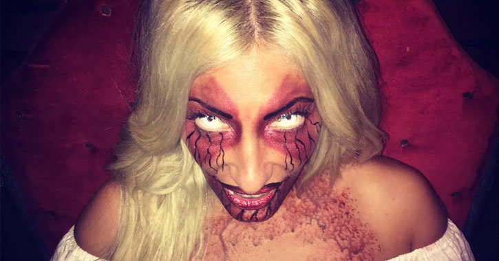 a scary demon-like girl with blonde hair and red and black makeup, empty eyes