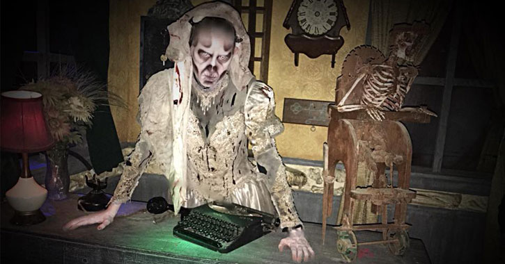 creepy white and gray creature standing over a keyboard ona  desk, skeleton next to him